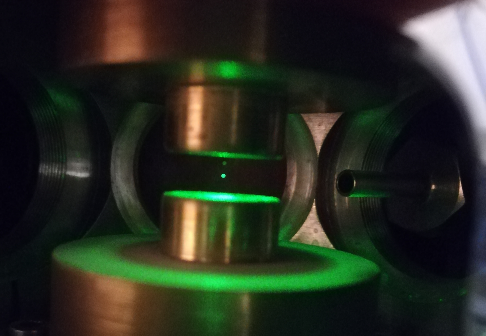 Particle floating in a chamber, illuminated by green laser light.