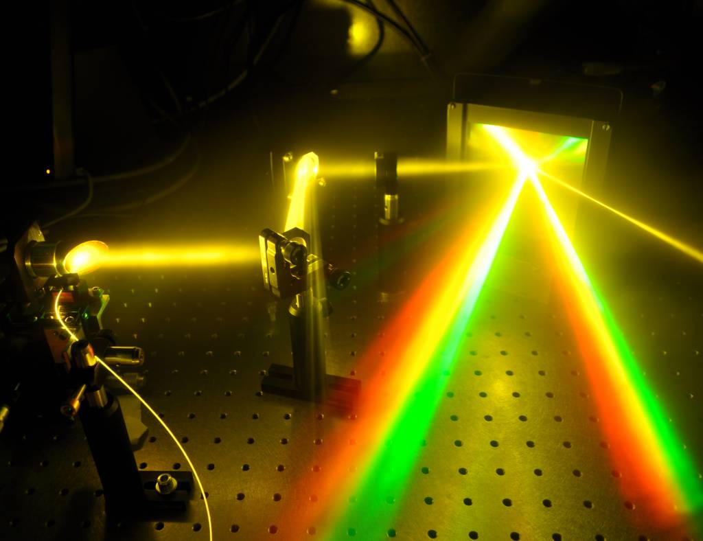 Illustration of directionality and wide spectral bandwidth of a supercontinuum source. Supercontinuum light is guided from an optical fiber into a parabolic mirror, which collimates the light. Radiation beam is white and has a diameter of 2 cm. Supercontinuum light propagates few tens of centimeters and reflects from two mirrors. Light is then focused into a diffraction grating, which reflects the wavelenghts of the supercontinuum into different directions showing two rainbows.