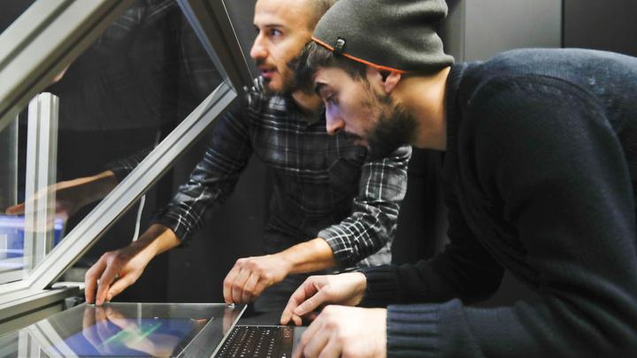 Two researchers working on a HUD display at CIVIT lab