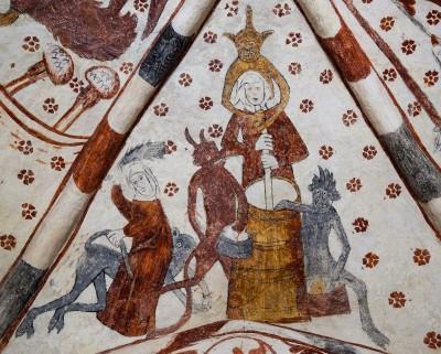 Kuvassa on valkoisella pohjalla oleva keskiaikainen kirkkomaalaus kirkon katon kattoruoteiden välissä. Keskellä kuvaa on kirnuava nainen, jota ympäröi neljä paholaishahmoa.